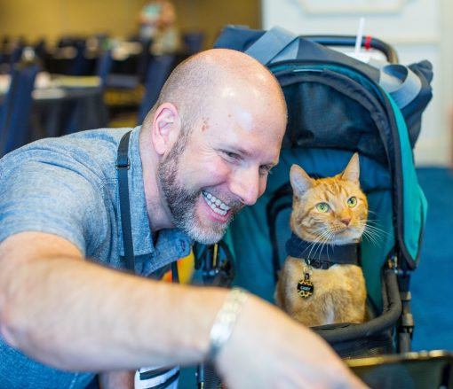Dr. Jason Nicholas smiles and interacts with orange boy-cat Casey riding in his blue cat stroller.